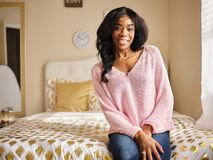 Retrato de la mujer afroamericana joven que se sienta en la sonrisa de la cama foto de archivo