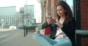 Retrato de la mujer afroamericana joven que usa el teléfono, al aire libre Foto de archivo