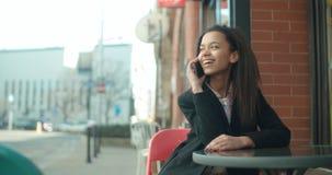 Retrato de la mujer afroamericana joven que usa el teléfono, al aire libre Fotografía de archivo libre de regalías