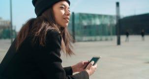 Retrato de la mujer afroamericana joven que usa el teléfono, al aire libre Imagen de archivo