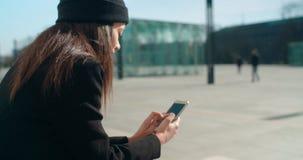 Retrato de la mujer afroamericana joven que usa el teléfono, al aire libre Imagen de archivo libre de regalías
