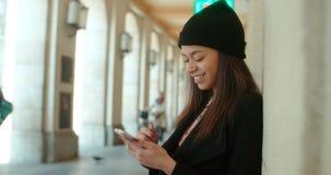 Retrato de la mujer afroamericana joven que usa el teléfono, al aire libre Fotos de archivo