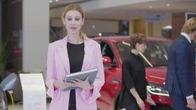Retrato de la mujer agradable en chaqueta rosada que explica la información sobre los coches in camera que detienen cierre grande almacen de metraje de vídeo