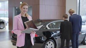 Retrato de la mujer agradable en la chaqueta rosada que mira en libro grande con la información sobre los coches delante de los p almacen de video