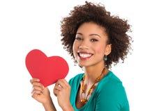 Mujer que lleva a cabo forma del corazón Imagen de archivo