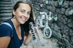 Retrato de la mujer alegre con la botella de agua y de outd sonriente Fotos de archivo libres de regalías