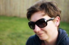 Retrato de la mujer alegre con las gafas de sol elegantes. Fotografía de archivo