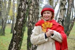 Retrato de la mujer alegre de los años medios con las hojas de arce amarillas en manos Fotografía de archivo libre de regalías