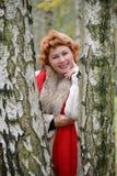 Retrato de la mujer alegre de los años medios entre abedules adentro Imagen de archivo