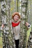 Retrato de la mujer alegre de los años medios entre abedules en t Fotografía de archivo libre de regalías