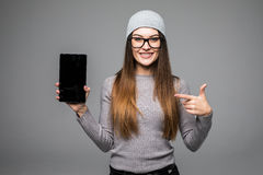 Retrato de la mujer alegre del inconformista que señala el finger en la pantalla de tableta sobre fondo gris Imagenes de archivo
