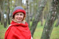 Retrato de la mujer alegre en una estola del rojo y un sombrero en un abedul Fotografía de archivo libre de regalías