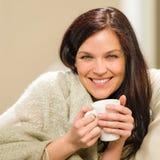 Retrato de la mujer alegre que bebe la bebida caliente fotos de archivo
