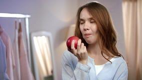 Retrato de la mujer alegre que come la manzana roja en casa Mujer sana que come la fruta almacen de video