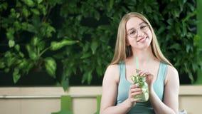 Retrato de la mujer apta joven bonita feliz que goza bebiendo el cóctel mezclado del detox que mira la cámara metrajes