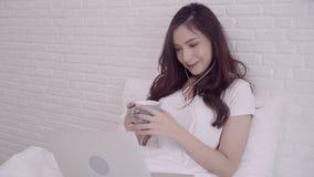 Retrato de la mujer asiática atractiva hermosa que usa el ordenador o el ordenador portátil que sostiene una taza caliente de caf almacen de video