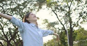 Retrato de la mujer asiática atractiva joven con la emoción feliz en un parque del verano metrajes