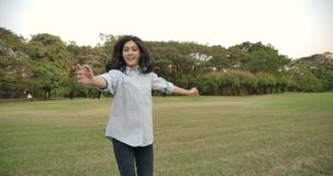 Retrato de la mujer asiática atractiva joven con la emoción feliz en un parque del verano almacen de video