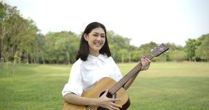 Retrato de la mujer asiática atractiva joven que toca la guitarra acústica en un parque del verano almacen de metraje de vídeo