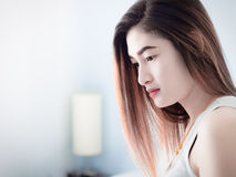 Retrato de la mujer asiática en el chaleco blanco, en su cama, expresando la idea del corazón quebrado y de la tristeza desespera fotografía de archivo