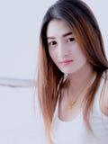 Retrato de la mujer asiática en el chaleco blanco, en su cama, expresando la idea del corazón quebrado y de la tristeza desespera fotos de archivo