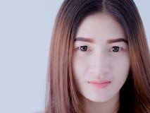 Retrato de la mujer asiática en el chaleco blanco, expresando la idea del corazón quebrado y de la tristeza desesperado y aguarde foto de archivo