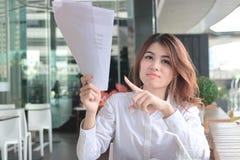 Retrato de la mujer asiática joven atractiva del empleado que señala papeleo o cartas en sus manos en oficina imagen de archivo