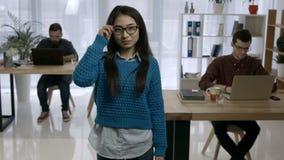 Retrato de la mujer asiática joven atractiva en la oficina almacen de video