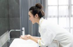 Retrato de la mujer asiática joven feliz mientras que se lava la cara y mira para duplicar en el cuarto de baño Cuidado de piel y imagen de archivo libre de regalías