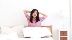 Retrato de la mujer asiática joven hermosa que coloca la ventana y sonrisa mientras que despierte con salida del sol en la mañana almacen de video