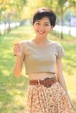 Retrato de la mujer asiática joven y hermosa que se coloca en ingenio del parque Fotografía de archivo libre de regalías