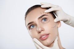 Retrato de la mujer atractiva con la línea discontinua y las manos de la cirugía plástica Fotos de archivo libres de regalías