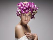Retrato de la mujer atractiva con las orquídeas en su peinado Foto de archivo
