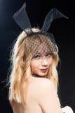 Retrato de la mujer atractiva con la parte posterior desnuda en una máscara y con el conejo Fotos de archivo libres de regalías