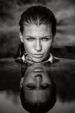 Retrato de la mujer atractiva en agua con la reflexión de la cara Fotos de archivo