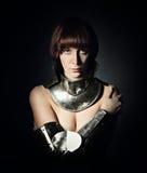 Retrato de la mujer atractiva en armadura sobre fondo negro Fotos de archivo