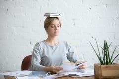 Retrato de la mujer atractiva en el escritorio, libros en su cabeza Fotos de archivo