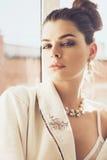 Retrato de la mujer atractiva en joyería y traje cerca de la ventana Fotos de archivo