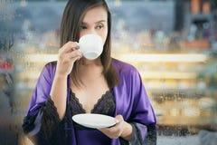 Retrato de la mujer atractiva en un traje púrpura del camisón y de seda que sostiene una taza blanca de té en un fondo blanco imágenes de archivo libres de regalías