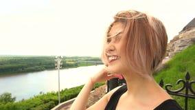 Retrato de la mujer atractiva joven con el pelo al aire libre de la sonrisa hermosa que sopla en viento almacen de metraje de vídeo