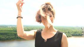 Retrato de la mujer atractiva joven con el pelo al aire libre de la sonrisa hermosa que sopla en viento metrajes