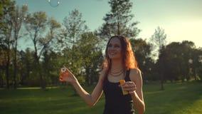 Retrato de la mujer atractiva joven del redhair hermoso Burbuja del soplo en el parque metrajes