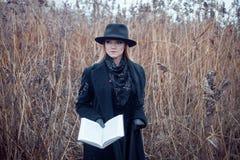 Retrato de la mujer atractiva joven en capa y sombrero negros Ella es una en un libro de lectura del campo, paisaje del otoño, hi Imagenes de archivo