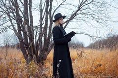 Retrato de la mujer atractiva joven en capa y sombrero negros Ella es una en un libro de lectura del campo, paisaje del otoño, hi Imagen de archivo