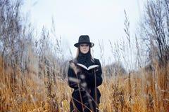 Retrato de la mujer atractiva joven en capa y sombrero negros Ella es una en un libro de lectura del campo, paisaje del otoño, hi Fotografía de archivo