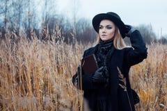 Retrato de la mujer atractiva joven en capa y sombrero negros Ella es una en un libro de lectura del campo, paisaje del otoño, hi Fotos de archivo