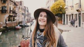 Retrato de la mujer atractiva joven feliz que sonríe, tomando una foto con la cámara profesional por el canal famoso de Venecia,  almacen de video