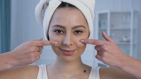 Retrato de la mujer atractiva joven que aplica la crema de cara en los pómulos almacen de metraje de vídeo