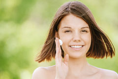 Retrato de la mujer atractiva joven que pone la crema en su cara Foto de archivo libre de regalías