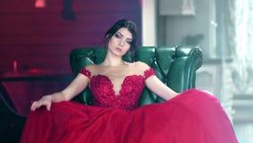 Retrato de la mujer atractiva de la moda en el vestido de igualación rojo del encanto que se sienta en la butaca que mira la cáma almacen de video